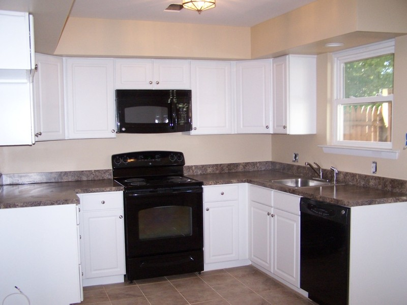 black kitchen cabinets and white appliances photo - 3